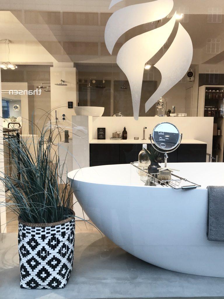 Vinduesudstilling hos Bad og Stil. Hvidt badekar med badeværelsesinteriør. Stylet af Salesstyling.